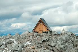 a frame cabin crowns alpine mountaintop