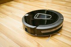 Robot Vacuum Cleaner On Laminate Wood Floor Royalty Free Stock Photos