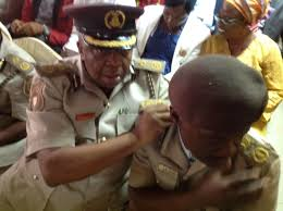 ia immigration service decorates officers news agency of mr king ekpedeme the spokesman of nis helping a colleague to adjust the new rank