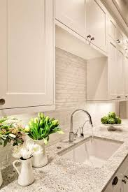 kashmir white granite with a glass tile backsplash and chrome faucet