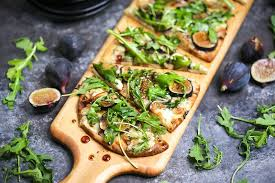 close up of fig blue cheese and arugula flatbread sliced and served on a