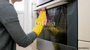 closeup photo of young woman with in yellow gloves washing dirty stained glass oven door