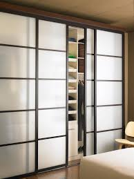 milky glass sliding door with black wooden frame on brown painted wall as well