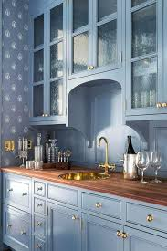 blue butlers pantry features cabinets upper accented with seeded glass cabinet doors adorned brass knobs paired wood panels for