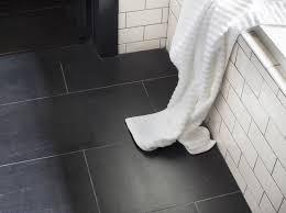 original brick patterned black bathroom floor tiles and white towel
