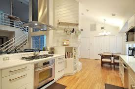white cabinets with open shelving solid countertop hanging pans and pots slide in range light wood flooring metallic vent hood brick wall kitchen