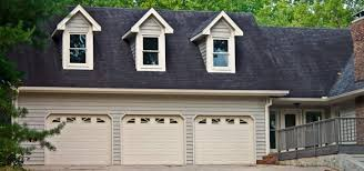 a garage with three doors attached to a house