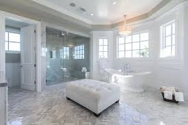 master bathroom with tray ceiling chandelier freestanding tub and herringbone tile floors