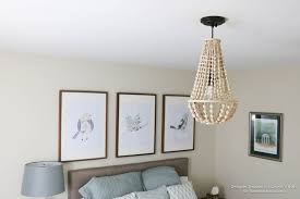 come learn how to make your own wood bead chandelier with this awesome tutorial
