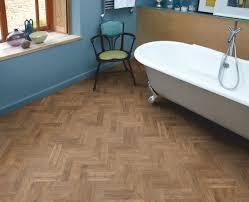 bathroom design idea with clawfoot bathtub and brushed oak herringbone vinyl wood floor by amtico