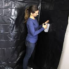 a woman using a staple to install a new vapor barrier for the wall