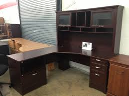 dark brown l shaped desk with hutch and storage with silver handle plus computer or laptop