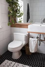 bathroom black floor tile in little white hexagon pattern white brick pattern wall modern white square sink oak
