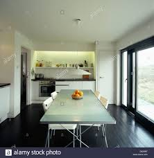 Kitchen And Dining Room Flooring White Chairs At Opaque Glass Topped Table In Modern Kitchen Dining