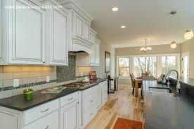 beautiful white kitchen cabinets with white subway tile backsplash and honed granite with wood flooring