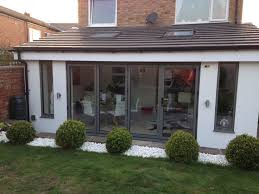 living room extension. a set of bifolding doors in grey aluminium closed and looking from the outside living room extension