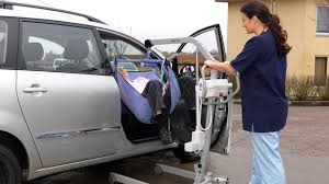 arjohuntleigh patient transfer solutions caregiver using maxi lite to lift patient resident into a car 3