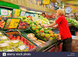 riga interior of rimi hypermarket n store assistant interior of rimi hypermarket n store assistant stacking shelves at fresh fruit and vegetable counter stall