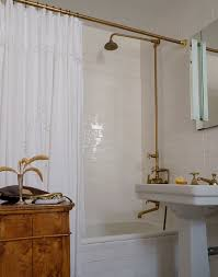 vintage style bathroom boasts subway tiled drop in bathtub with brass exposed plumbing shower kit as well as brass shower rod dressed in white ruffled