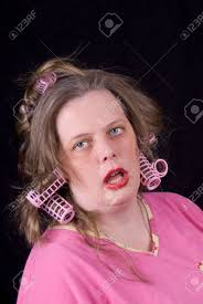 stock photo woman wearing hair curlers and extreme makeup making a funny face isolated over black