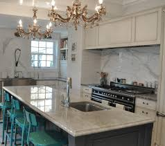 chic kitchen with amber crystal chandeliers over gray kitchen island with mother of pearl quartzite prep sink and turquoise industrial bar stools