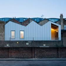 delvendahl martin architects adds studio flat with jagged roof to artists work a jagged corrugated metal clad