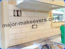 kitchen backsplash tile installation in progress countertops protected with towels
