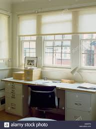 White Blinds At Window Above Black Chair And Desk With Storage Boxes