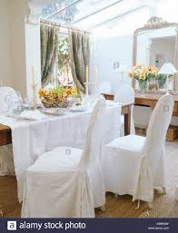dining room chairs with loose covers. stock photo - white loose covers on chairs at table with linen cloth in small conservatory dining room e