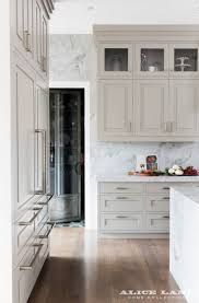 Marble waterfall countertop with beige kitchen cabinets