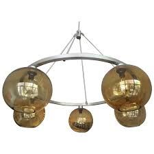 a sculptural chandelier with a decidedly modern edge this stunning 5 light suspended fixture boasts oversized glass globes with edison style bulbs and a