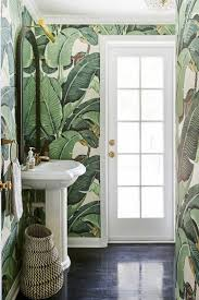 Fabulous powder room features walls clad in Martinique Banana Leaf Wallpaper  lined with a white pedestal sink and an arched black mirror illuminated by  a ...