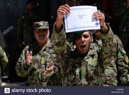 an afghan national army ier holds up his diploma marking him  an afghan national army ier holds up his diploma marking him as an honor graduate during