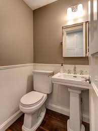 crisp clean lines and neutral colors dominate this small traditional powder room the pedestal