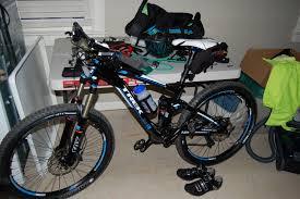 My mountain bike in the garage leaning against a table full of bike stuff
