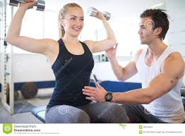 gym instructor gym instructor supporting woman in lifting weights stock photo