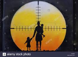 wall art graffiti in brick lane london silhouette of a mother holding her children with a sniper riffle target on them  on target childrens wall art with wall art graffiti in brick lane london silhouette of a mother stock