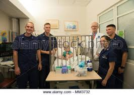 Coast Guard officers stand next to Brannon Morgan, a dialysis ...