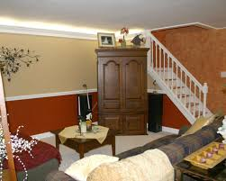 split level diy small basement remodel design for living room spaces design with brown wood cupboard under white staircase and small oak table in the middle