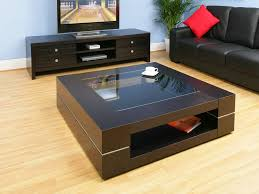 large square coffee table with espresso colour near tv stands with storage and black leather sofa plus potted plants in the corner with wooden vinyl