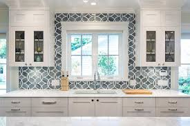 white shaker cabinets painted benjamin moore white heron paired with princess white quartzite countertops and an ann sacks beau monde glass polly tiles