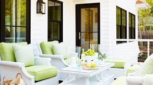 Green is tantamount to nature, and on this elevated porch, where nostalgic  white wicker