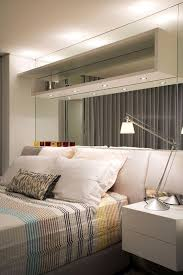 Fashioned Small Apartment Bedroom Design Interior Using Stripes Bedding  Also Wall Mirror And White Cushions Plus