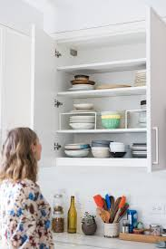 plates bowls and dishes on a shelf with organizing risers