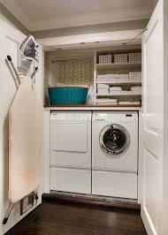 double closet doors open to reveal a small and efficient laundry room filled with a miele washer and dryer tucked under a small shelves with backs of