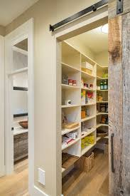 View from hallway into walk-in pantry framed by a salvaged wood sliding  barn door