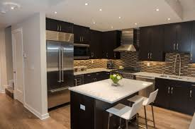 cabinet and lighting. black wood cabinetry and island contrast with patterned tile backsplash white marble countertops cabinet lighting k