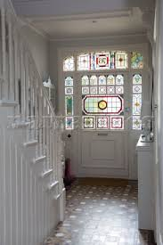 stained glass front door in white hallway entrance of hertfordshire home england uk