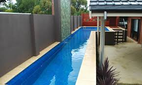 Long swimming lap pool with accent wall waterfall