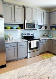 Fun Kitchen with gray shaker cabinets paired with granite countertops and  blue glass subway tile backsplash. Kitchen features microwave over  stainless steel ...